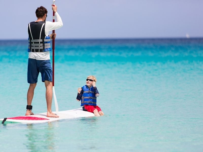 paddle boarding man and boy
